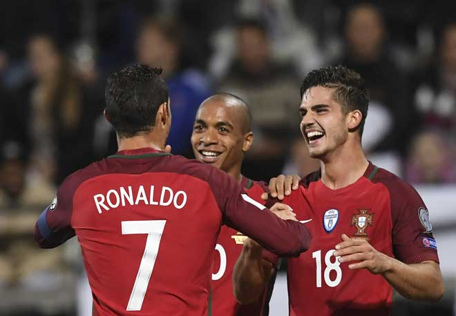 Cristiano Ronaldo und Mittelfeldspieler Joao Mario (C) gratulieren Portugals Stürmer Andre Silva (R) zum Torschuss in Torshavn (Färöer Inseln) am 10 Oktober 2016. / AFP PHOTO / FRANCISCO LEONG