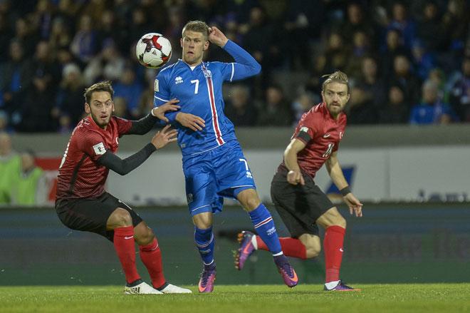 Islands Stürmer Johann Berg Gudmundsson (M) wetteifert mit dem türkischen Mittelfeldspieler Hakan Calhanoglu (L) um den Ball. / AFP PHOTO / Haraldur Gudjonsson
